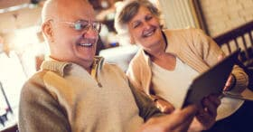 Happy senior couple sitting at home and using touchpad together.